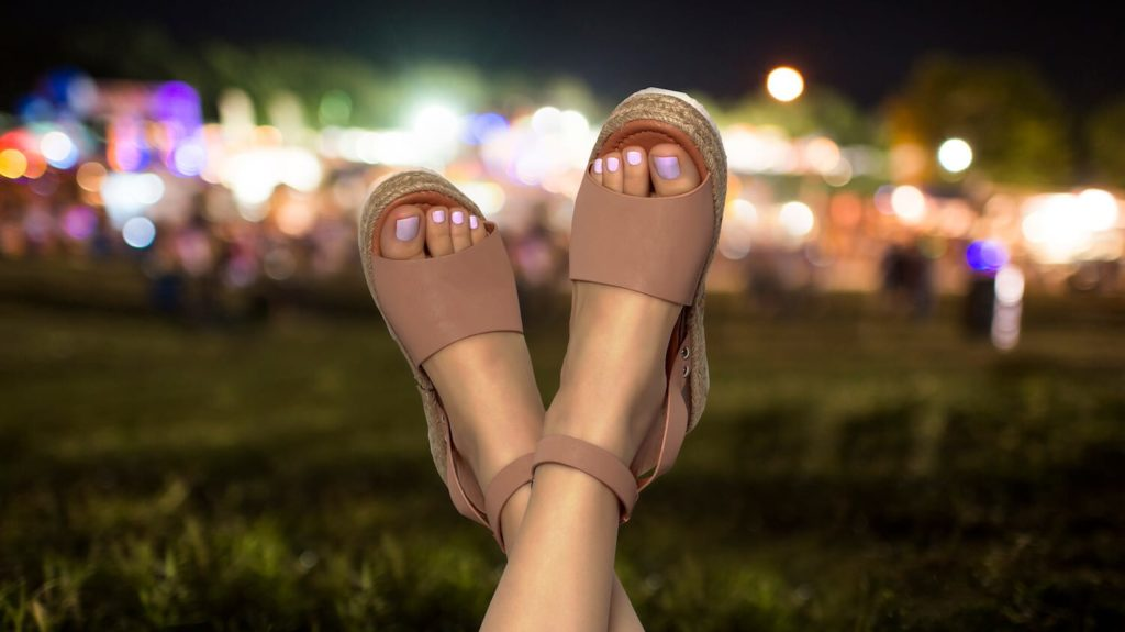 Sandaled feet with party lights in the background